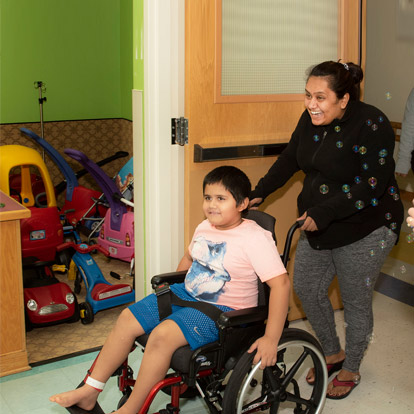 mother pushing son in wheelchair