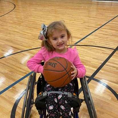 paciente de sexo femenino en silla de ruedas sosteniendo una pelota de básquet