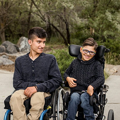 two boys in wheelchairs, outside