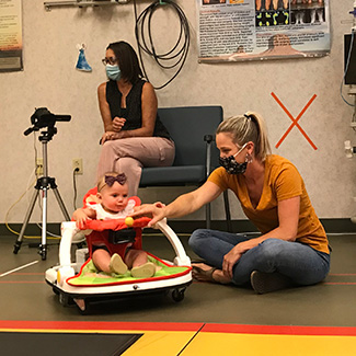patient in Baby Bug with mom and staff member