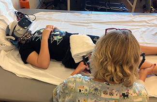Karley wearing VR goggles during therapy