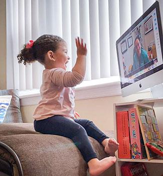 Riley waving at screen during video visit
