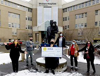 staff members with giant check in front of hospital