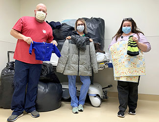 Three staff members displaying donations