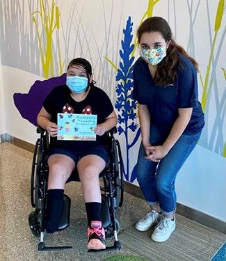 Lauren with patient holding book
