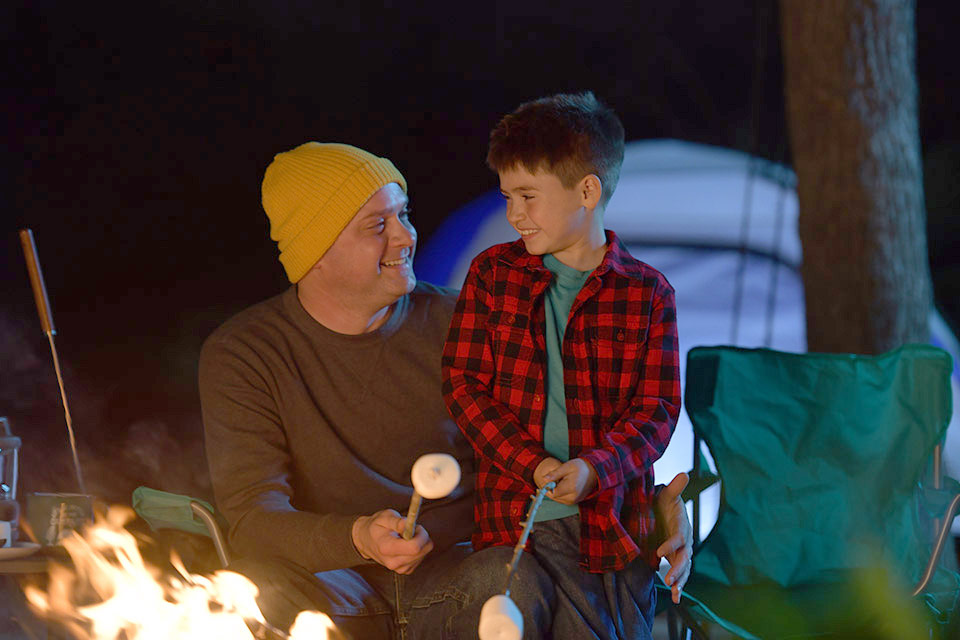father and son roasting marshmallows over campfire