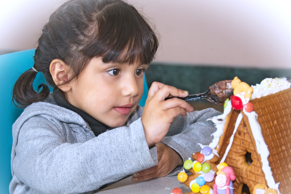 Female patient decorating a gingerbread house
