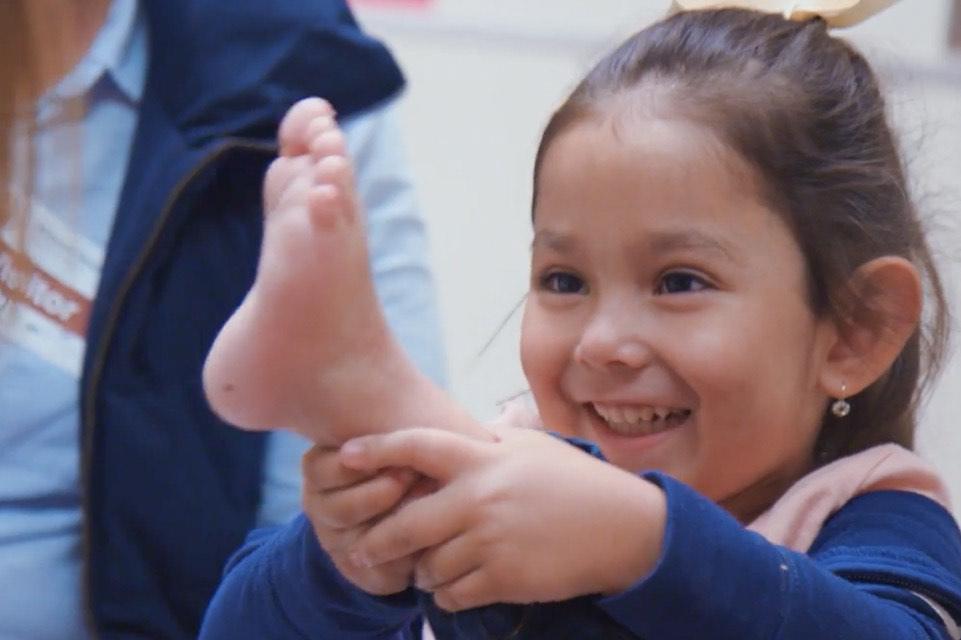 Little girl holding her foot